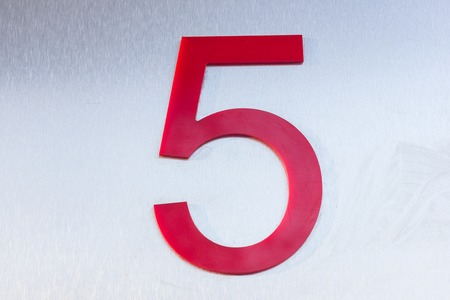 Red number five on a sheet of stainless metal. Position. Serial number. Place in space Standard-Bild