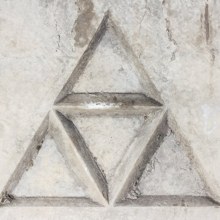 A fragment of concrete fence. Tracery pattern of stone wall as triangle. Part of the wall.