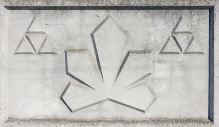 A fragment of concrete fence. Tracery pattern of stone wall as triangle.