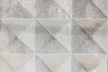 Hintergrundbeschaffenheit des alten grauen konkreten Zauns mit quadratischem Muster. Geometrisches Muster Standard-Bild - 74993115