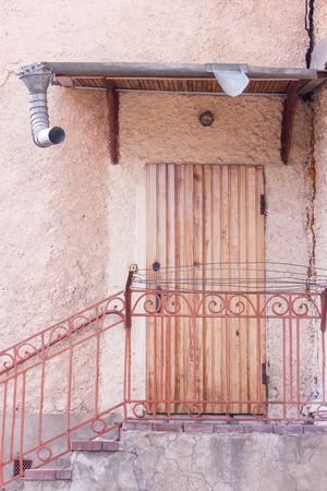 Entrance to the building through a brown wooden door. Steps with metal handrail Standard-Bild