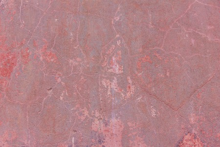 Red concrete wall with cracks. Abstract red background