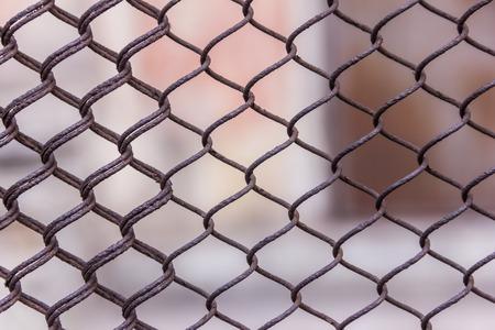 Rostiges Stahlkettenglied oder Maschendraht als Begrenzungswand. Hinter dem Netz befindet sich noch eine Betonsteinwand. Beste Sicherheit Standard-Bild - 75044042