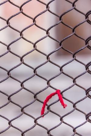 Rostiges Stahlkettenglied oder Maschendraht als Begrenzungswand. Roter Faden. Hinter dem Netz befindet sich noch eine Betonsteinwand. Beste Sicherheit Standard-Bild - 75044007
