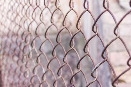 Rostiges Stahlkettenglied oder Maschendraht als Begrenzungswand. Hinter dem Netz befindet sich noch eine Betonsteinwand. Beste Sicherheit Standard-Bild - 75044004
