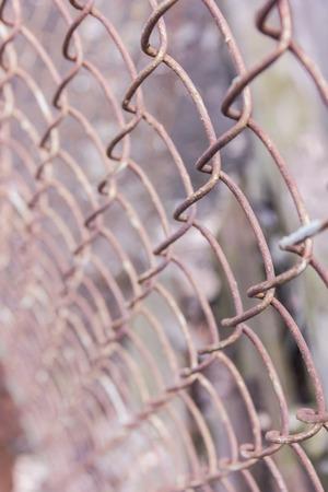 Rostiges Stahlkettenglied oder Maschendraht als Begrenzungswand. Hinter dem Netz befindet sich noch eine Betonsteinwand. Beste Sicherheit Standard-Bild - 75722565