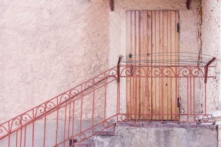 Eingang zum Gebäude durch eine braune Holztür. Schritte mit Metall Handlauf Standard-Bild - 74995045