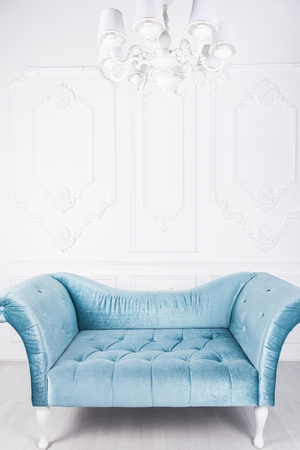 Blue sofa in white interior and gray floor