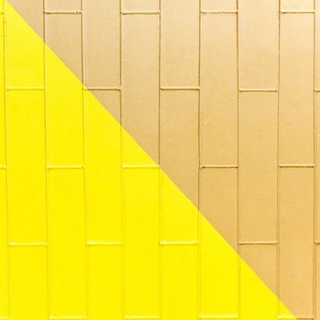 Gelbe und braune Backsteinmauerbeschaffenheit. Zweifarbiger abstrakter Hintergrund Standard-Bild - 75840387