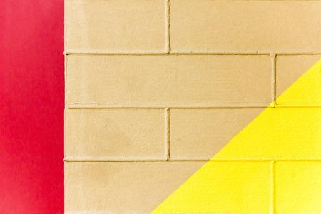 Gelbe und braune Backsteinmauerbeschaffenheit mit roter Linie. Dreifarbiger abstrakter Hintergrund Standard-Bild - 76652183