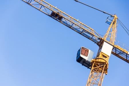 High tower crane against the blue sky. Fragment of a crane Standard-Bild