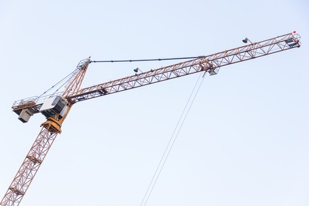 High tower crane against the blue sky