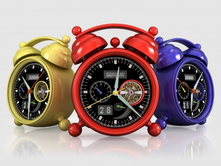 Three alarm clocks, red, yellow, dark blue, with a mechanical mechanism on a gray background with reflection photo