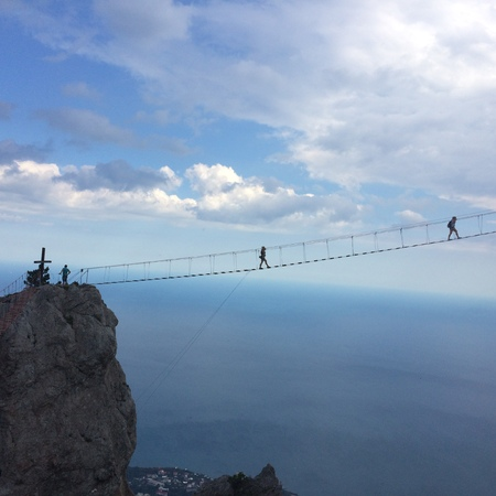 Walking on a wooden suspension bridge. High in the mounteins