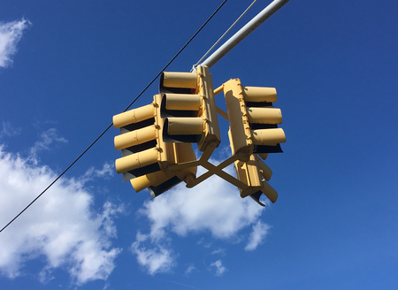 stop and go light: Traffic light hanging against sky
