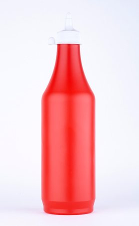 Red plastic ketchup bottle on a white background Stock Photo