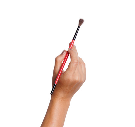 Isolated hand holding a paintbrush. Brush painting on white background.