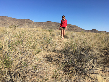 Beautiful girl is walking in the Arizona desert at the noon.