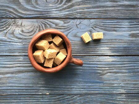 pieces of brown sugar in a ceramic mug on a wooden background 免版税图像