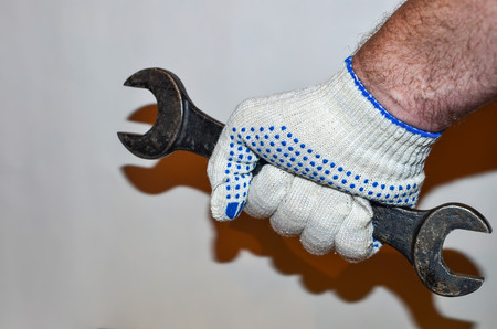 Spanner in the hand of a man in a white glove on a white wall background .. Construction tools. Plumber