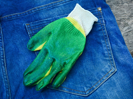 Construction white glove on the background of a pocket of blue jeans Stockfoto