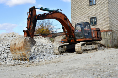 Construction excavator at an industrial gypsum stone processing plant. Mineral Loading