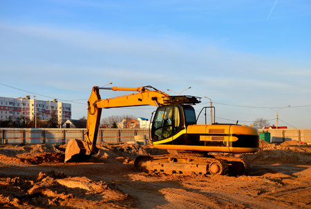 Tracked excavator with a bucket in the ground at a construction site against a blue sky and sunset