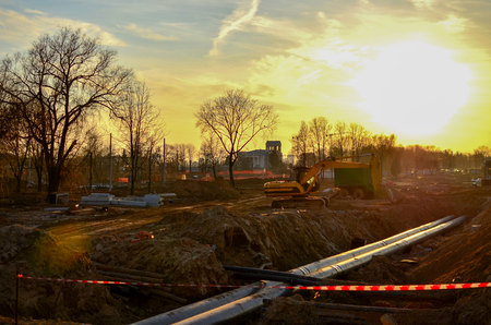 Tracked excavator with a bucket in the ground at a construction site during the laying of sewer pipes in the ground, against a blue sky and sunset. Engineering and heating systems