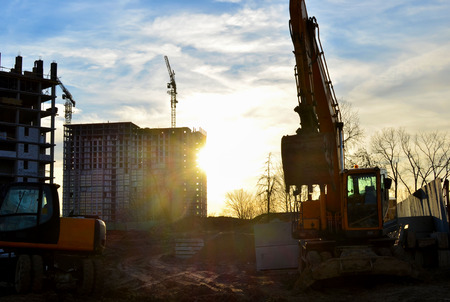 Tracked excavator with raised bucket. Construction earthmoving equipment at the construction site against the backdrop of sunset and the rays of the sun