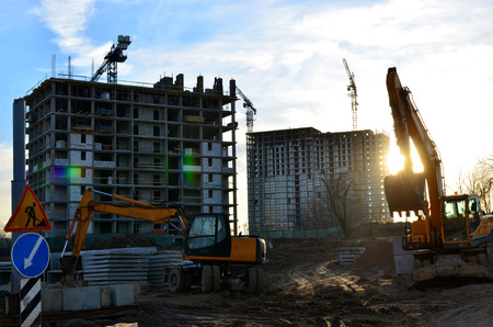 Two backhoe loaders during excavation work on the construction site of high residential buildings and offices. Sunset at a construction site