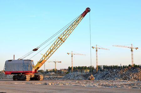 Großer Raupenkran oder Schleppbagger mit einer schweren Abrissbirne aus Metall an einem Stahlseil. Abrissbirnen auf Baustellen. Demontage und Abriss von Gebäuden und Bauwerken - Image