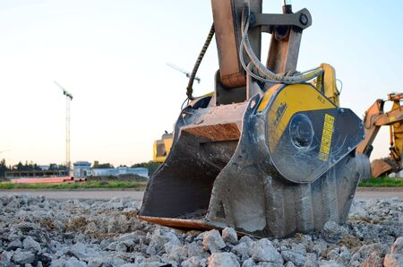 Crushing bucket of the excavator for crushing concrete. Construction waste recycling for construction mix. Sifting and grinding bucket for the separation of concrete into fractions of higher quality.