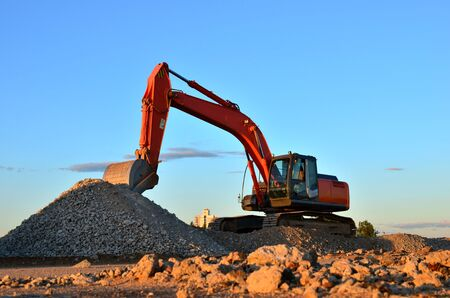 Large tracked excavator works in a gravel pit. Loading of stone and rubble for its processing at a concrete factory into cement for construction work. Cement production factory on mining quarry