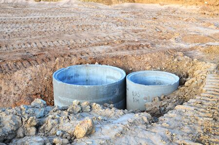 Installation of concrete sewer wells in the ground at the construction site. The use of reinforced concrete rings for cesspools, overflow septic tanks. Improvement of wells and storm sewage - Image