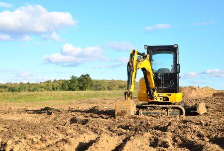 Minibagger, der Erde in einem Feld oder Wald gräbt. Verlegung von unterirdischen Abwasserrohren beim Bau eines Hauses. Graben von Gräben für eine Gas- oder Ölpipeline. Erdarbeiten, Baugrube Standard-Bild