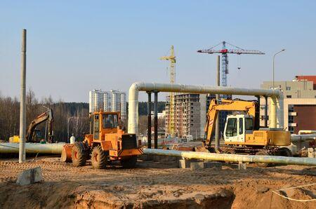 Schwere Baumaschinen und Erdbewegungsbagger arbeiten auf einer Baustelle in der Stadt. Verlegung oder Austausch von unterirdischen Regenwasserkanalrohren.