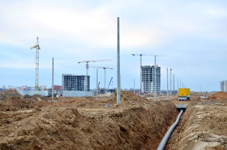 Laying of underground storm sewer pipes. Installation of water main, sanitary sewer. Plastic drainage pipe in ditch. Installation of concrete sewer wells in the ground at the construction site. Reklamní fotografie