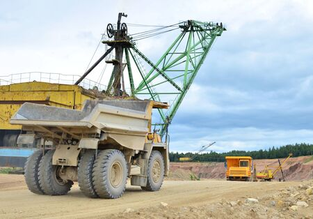 Huge mining excavator and dump trucks work in an open pit.  Loading and transportation of sand, gravel, dolomite and limestone to the place of processing and crushing. Mining industry - Image Stock Photo
