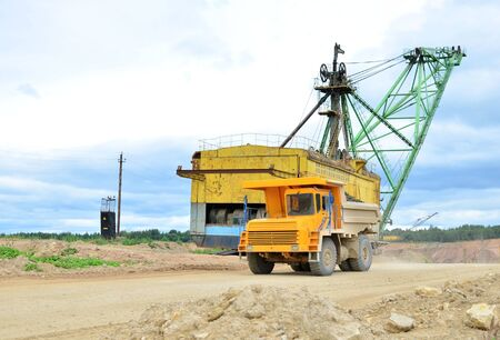Big yellow dump truck working in the limestone open-pit. Loading and transportation of minerals in the dolomite mining quarry. Belarus, Vitebsk, in the largest i dolomite deposit, quarry