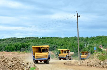 Big yellow dump trucks working in the limestone open-pit. Loading and transportation of minerals in the dolomite mining quarry. Belarus, Vitebsk, in the largest i dolomite deposit, quarry Gralevo