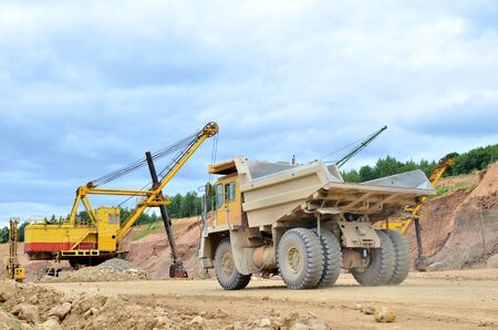 Big mining truck amid huge excavators in an open-pit  dolomite quarry. Loading and transportation of stone ore in a limestone quarry. Excavator and heavy mining dump truck Stock Photo