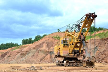 Huge mining excavator in the limestone open-pit. Biggest digger working in dolomite quarry. Largest tracked machine with electric shovel. Heavy duty electric-powered mining equipment - Image