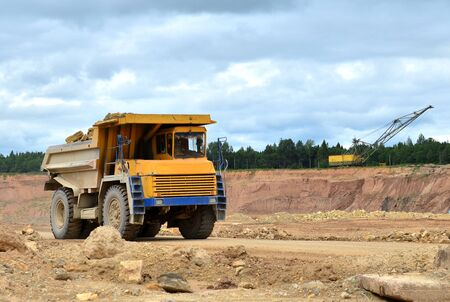 Big yellow dump truck working in the limestone open-pit. Loading and transportation of minerals in the dolomite mining quarry. Belarus, Vitebsk, in the largest i dolomite deposit, quarry Gralevo