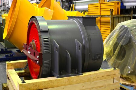 Synchronous traction generator with a cylindrical rotor in the production hall of an automobile plant. Electrical engines and equipment for heavy-duty mining trucks. Hydro Energy, permanent-magnet