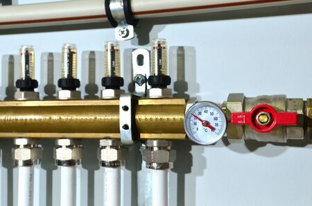 Close up of manometer, pipe, flow meter, water pumps and valves of heating system in a boiler room at home. Systems of water floor heating of  houses. Underfloor Heater Manifolds, background, texture