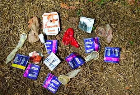 Discarded packages and used condoms roll on the ground in the park.