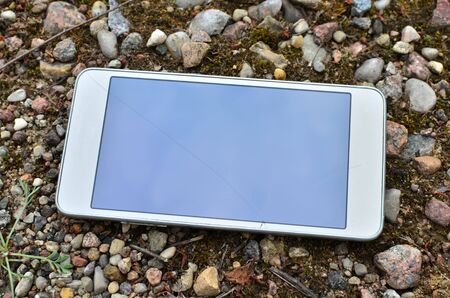 Mobile smartphone with a broken screen on the ground. Repair Gadgets Background 스톡 콘텐츠