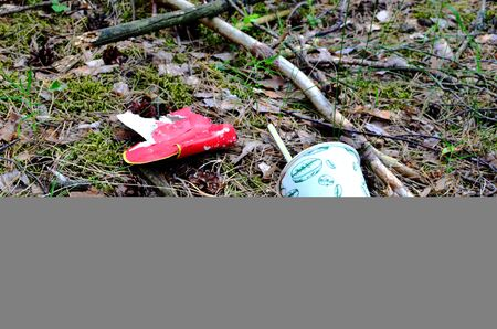 Discarded coffee cup and fast food packaging in the forest on ground. People left behind trash. The concept of pollution of nature and the environment, background, texture