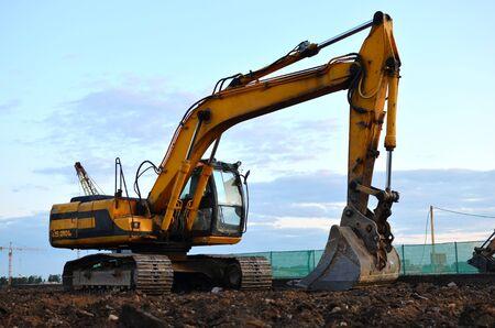 Großer Raupenbagger auf einer Baustelle. Straßenreparatur, Asphaltaustausch. Verladen von Stein und Schutt für seine Verarbeitung in einer Betonfabrik in Zement für Bauarbeiten.