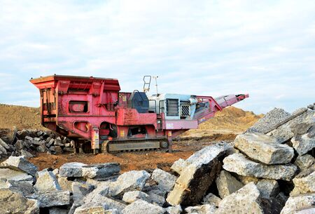 Mobile Stone crusher machine by the construction site or mining quarry for crushing old concrete slabs into gravel and subsequent cement production. Jaw crusher with conveyor belt